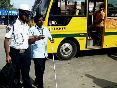 A Traffic Warden helping a visually challenged person cross the road